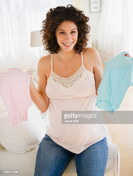 Pregnant woman holding up blue and pink onesies