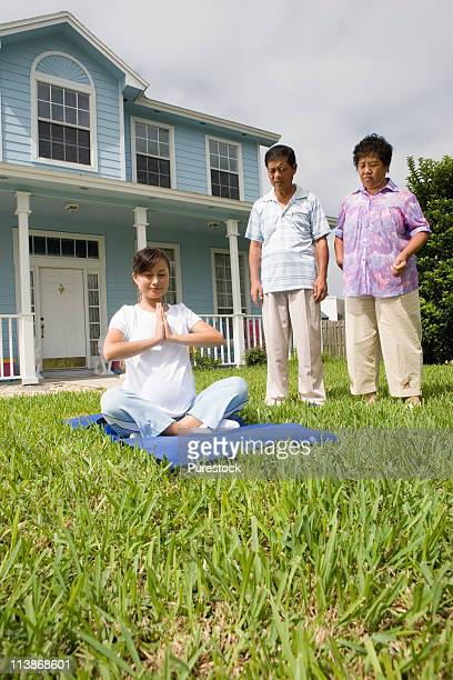Pregnant woman in a yoga position while her parents stand by and watch