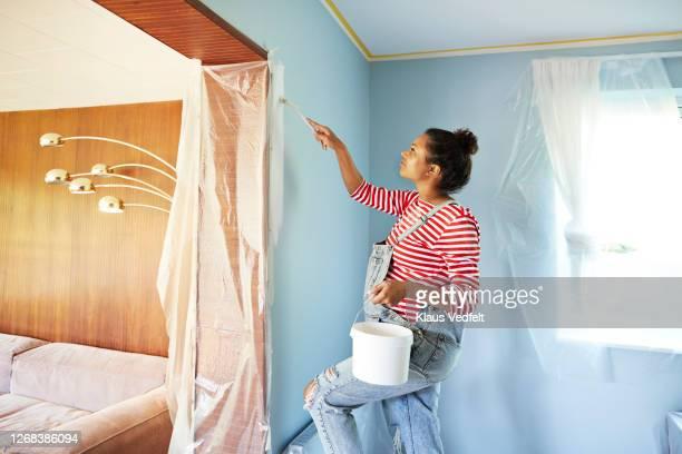pregnant woman in bib overalls renovating room - dedizione foto e immagini stock