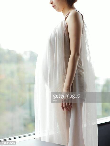 pregnant woman in front of window - see thru nightgown stock photos and pictures