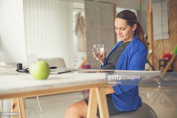 Pregnant woman in office drinking water