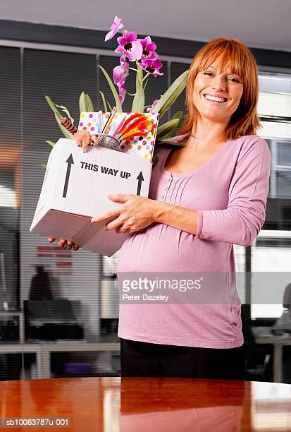 Pregnant woman in office holding box with personal things, portrait
