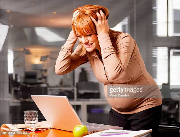 Pregnant woman in office, looking at laptop, head in hands