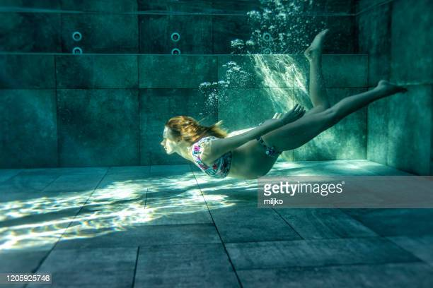 pregnant woman in swimming pool - miljko stock pictures, royalty-free photos & images