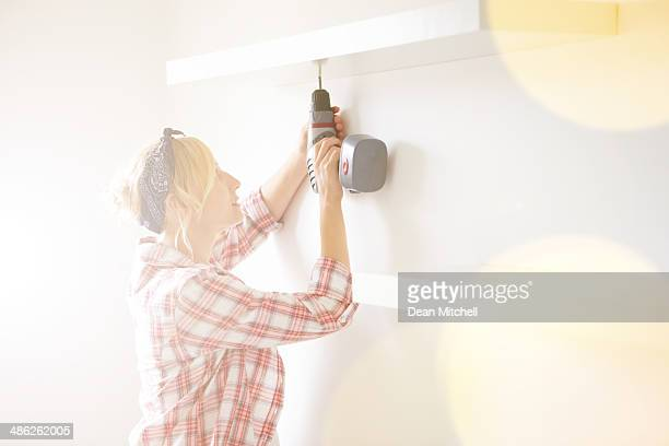 pregnant woman installing a shelf - drill stock pictures, royalty-free photos & images