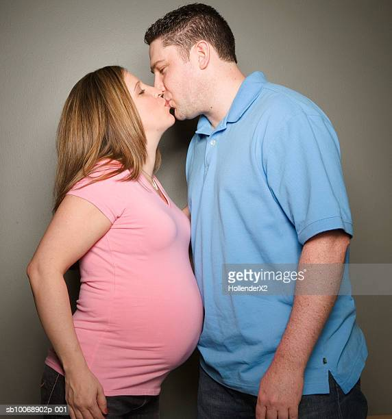 pregnant woman kissing man, profile, studio shot - men bulge stock photos and pictures