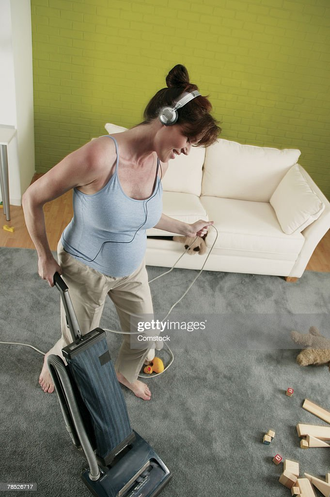Pregnant woman listening to music on portable device while vacuuming : Stock Photo
