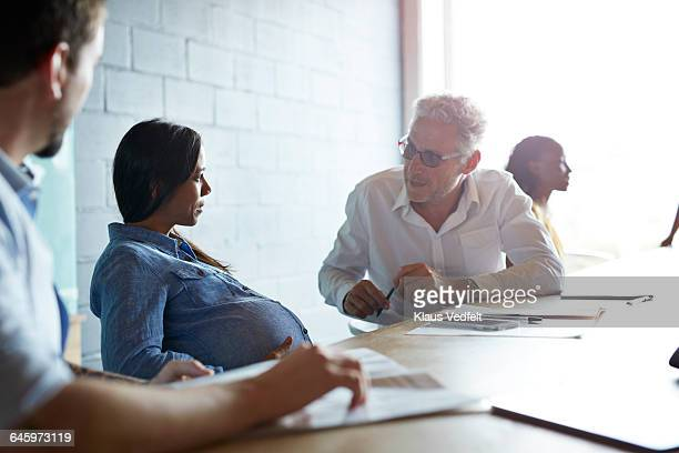 Pregnant woman listenning to co-worker