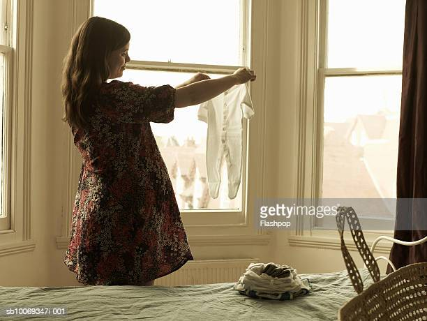 pregnant woman looking at babygrow - baby clothing stock pictures, royalty-free photos & images