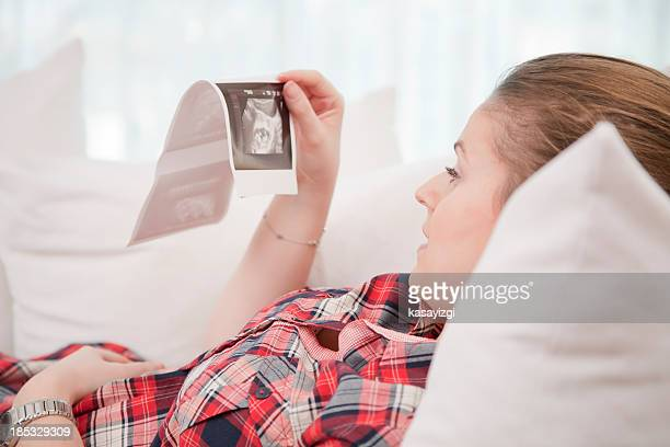 Pregnant woman looking at her babies photo