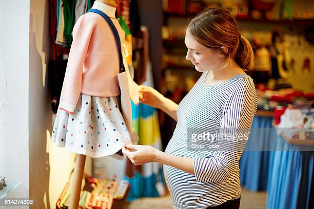 pregnant woman looking at kids' clothes - maternity wear stock pictures, royalty-free photos & images