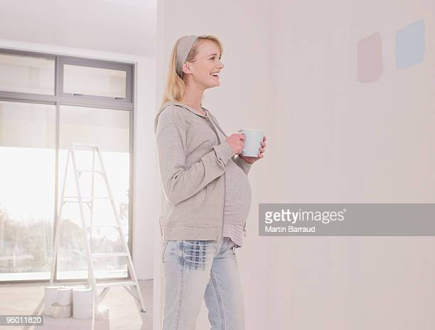 pregnant woman looking at paint samples on nursery wall - pregnant coffee stock pictures, royalty-free photos & images