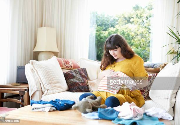 Pregnant woman looking through baby clothes at home.