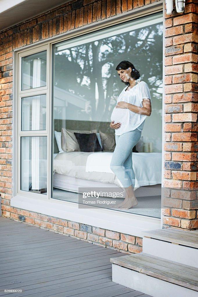 Pregnant woman looking through window : Foto de stock