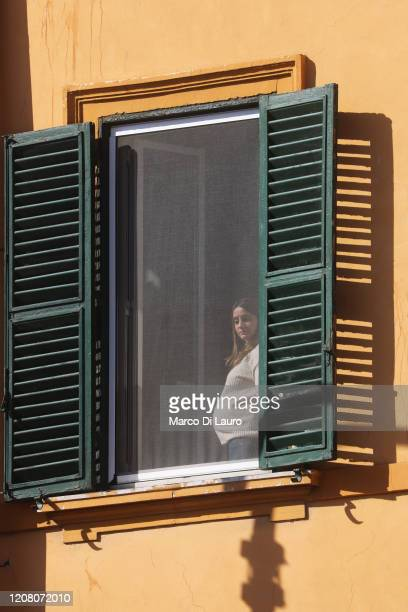 A pregnant woman looks out the window through a mosquito net during lockdown on March 23 2020 in Rome Italy As Italy extends its nationwide lockdown...