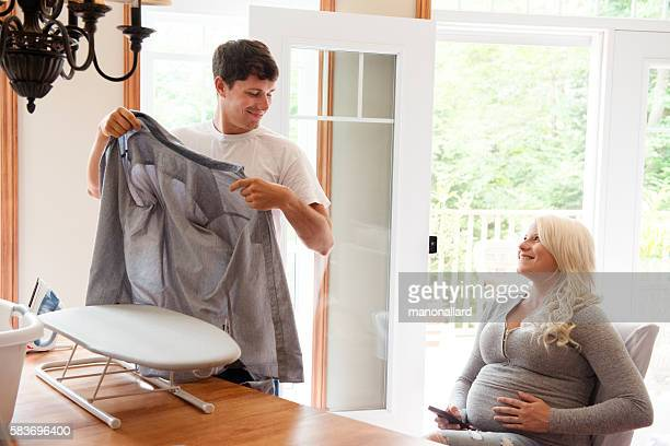 Pregnant woman looks tenderly at a man ironing linen