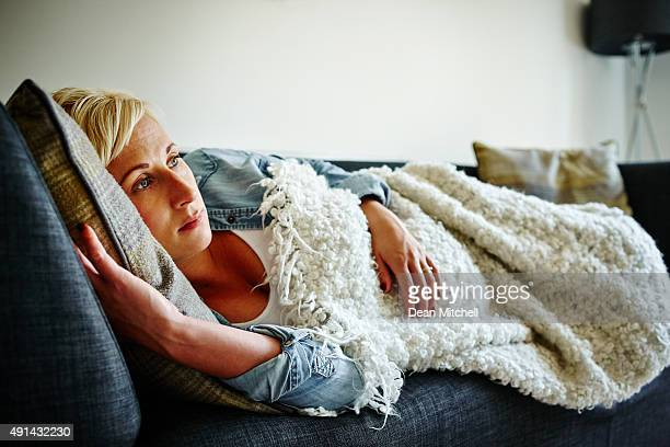 Pregnant woman lying on couch daydreaming