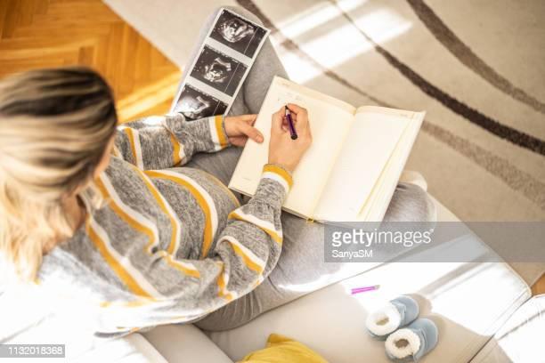 妊娠中の女性が行うリストを作る - マタニティウェア ストックフォトと画像