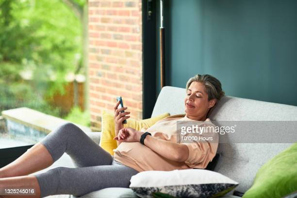 pregnant woman monitoring her pulse rate - one mature woman only stock pictures, royalty-free photos & images