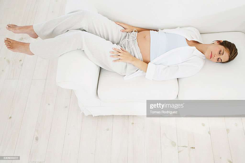 Pregnant woman napping on couch : Stock Photo
