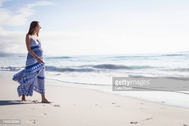 pregnant woman on beach, cape town, south africa - maxi dress stock pictures, royalty-free photos & images