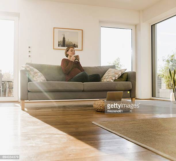 Pregnant woman on couch enjoying a drink in mug