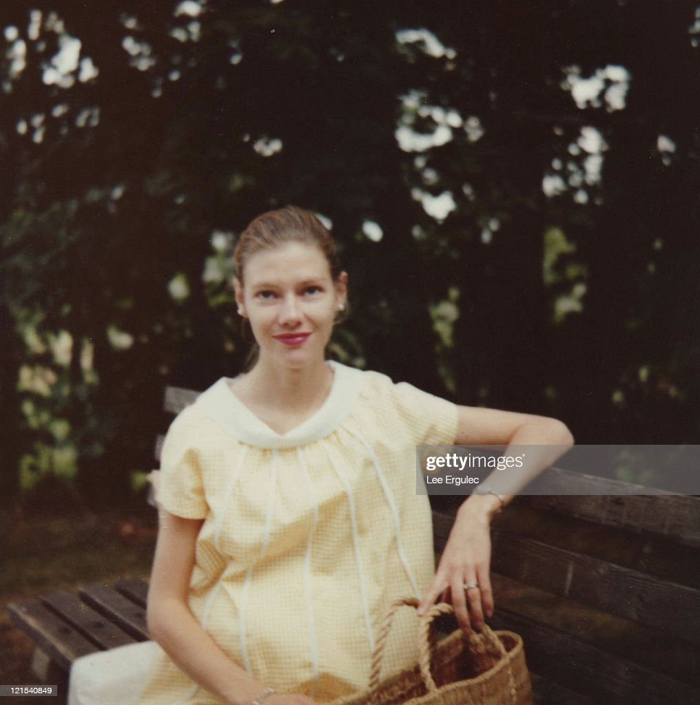 Pregnant woman on park bench : Stock Photo