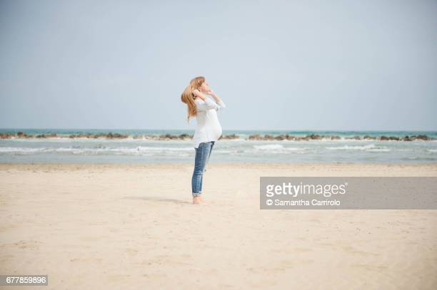 Pregnant woman on the beach. Casual clothes.