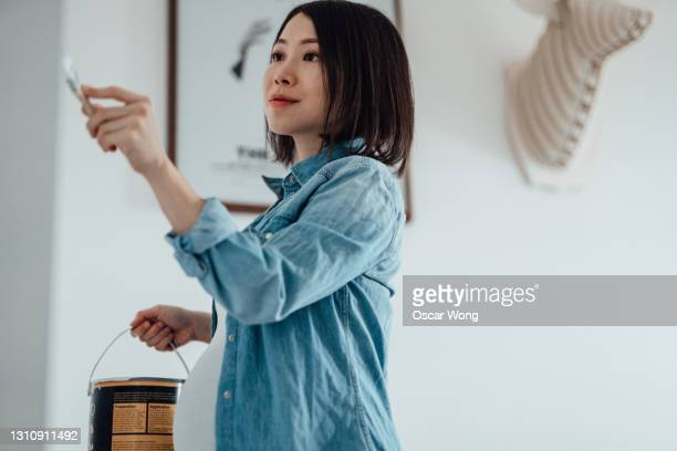 pregnant woman painting nursery room - asian and indian ethnicities stock pictures, royalty-free photos & images
