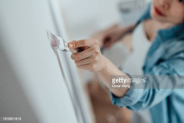 pregnant woman painting nursery room - human limb stock pictures, royalty-free photos & images