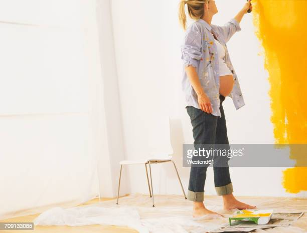 Pregnant woman paiting a wall