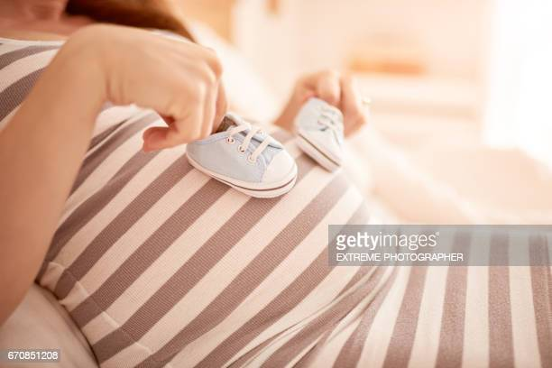 pregnant woman - baby booties stock photos and pictures
