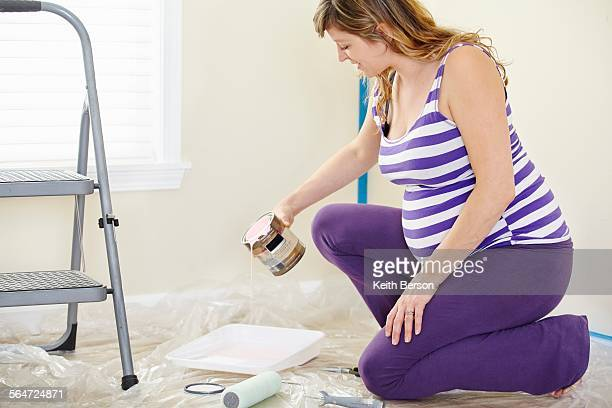 Pregnant woman pouring pink paint to decorate nursery