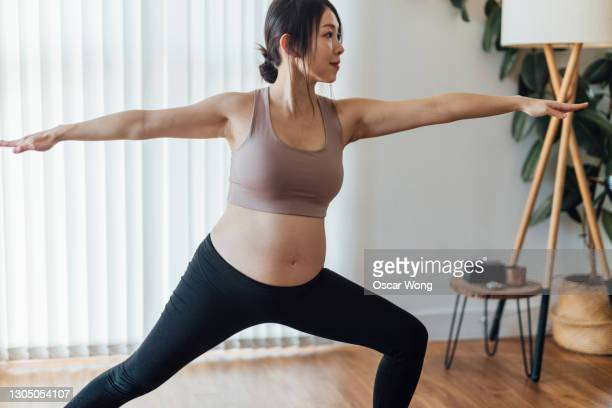 pregnant woman practices warrior 2 at yoga studio - active lifestyle stock pictures, royalty-free photos & images