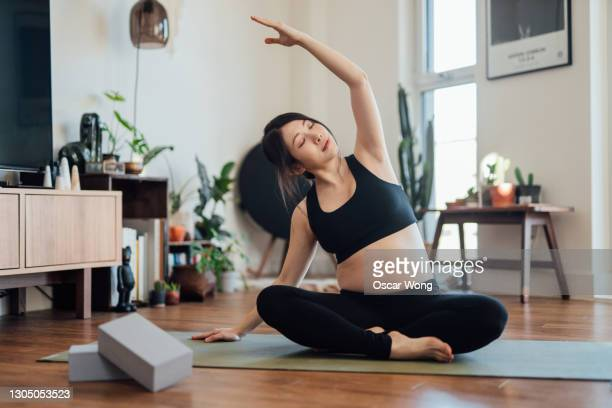 pregnant woman practices yoga at home - stretching stock pictures, royalty-free photos & images