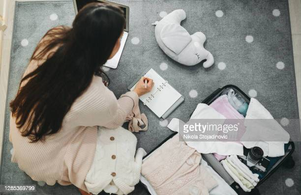 a pregnant woman prepares a bag for the hospital - bag stock pictures, royalty-free photos & images