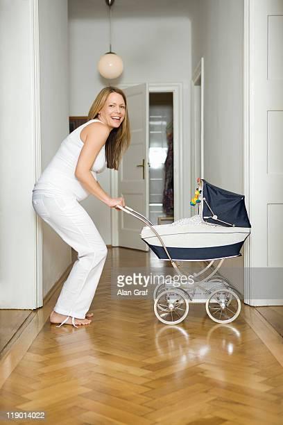 Schwangere Frau schieben Kinderwagen