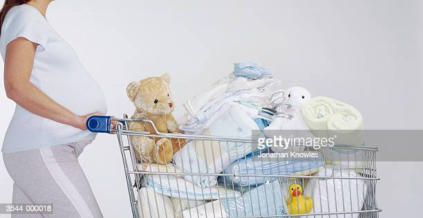 pregnant woman pushing cart - baby clothing stock pictures, royalty-free photos & images