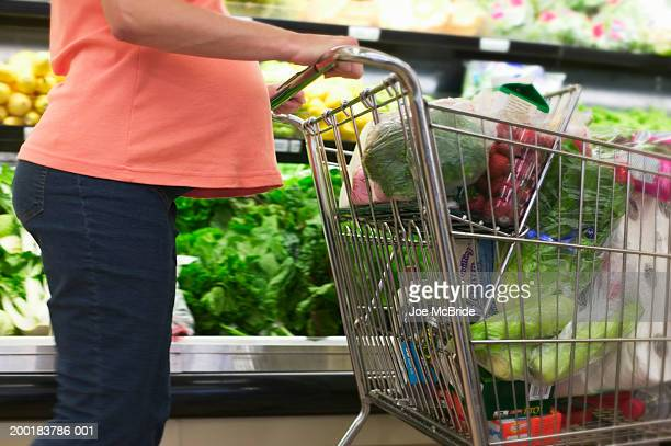 pregnant woman pushing shopping cart, mid-section - caddie rempli photos et images de collection