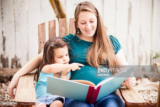 Femme enceinte lisant à Daugther dans l'arrière-cour