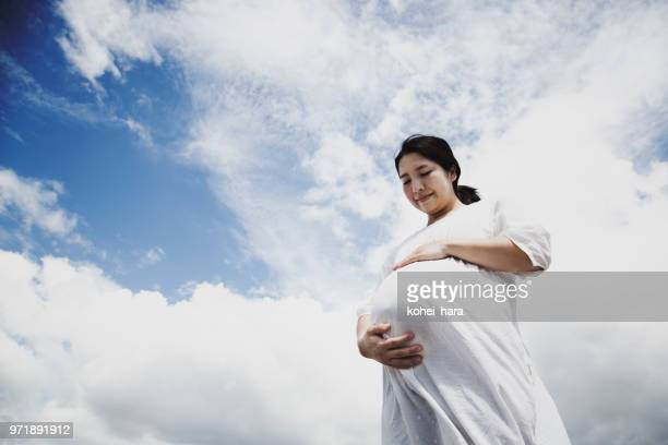 Pregnant woman relaxed under blue sky
