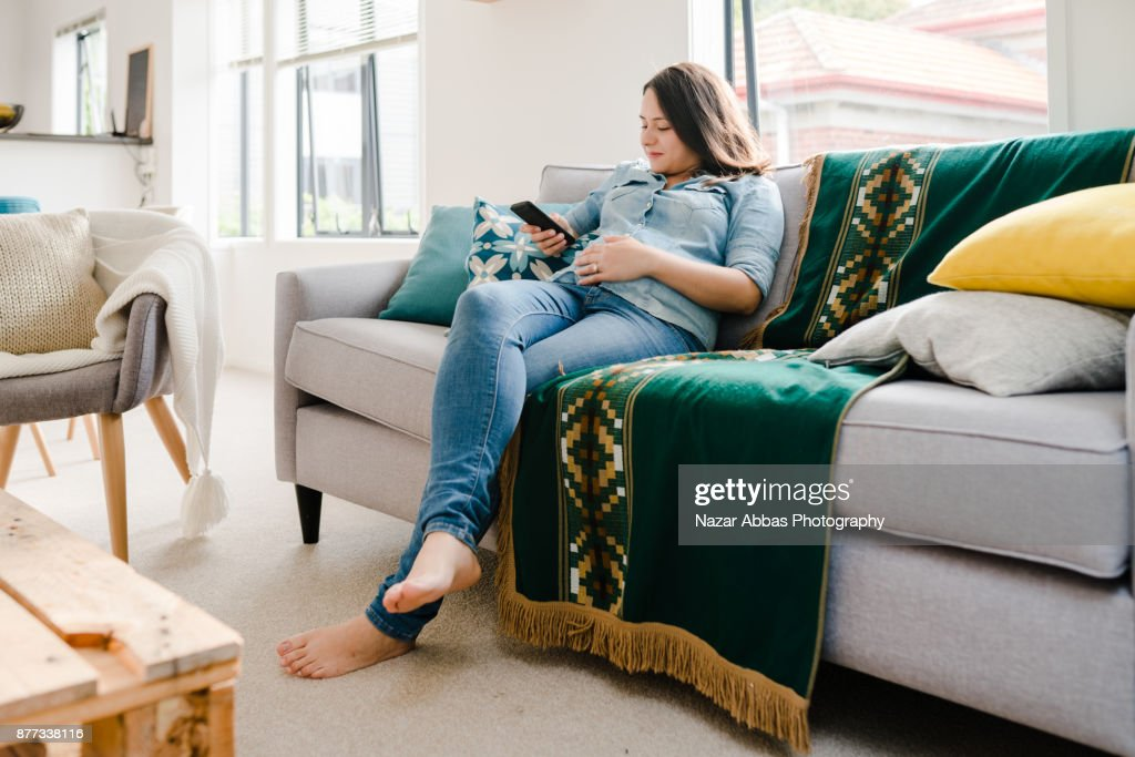 Pregnant woman relaxing at home with smartphone in her hand. : Stock Photo