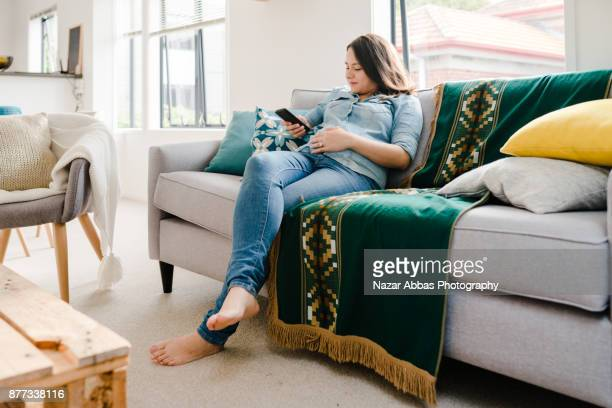Pregnant woman relaxing at home with smartphone in her hand.