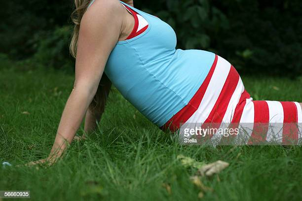 a pregnant woman relaxing in the grass - striped dress stock pictures, royalty-free photos & images