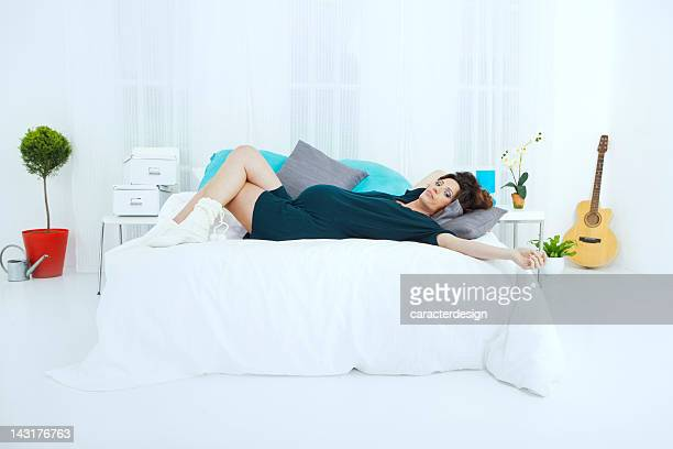 Pregnant woman resting on bed