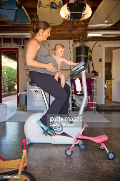 Pregnant woman rides stationary bike with toddler