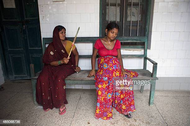 A pregnant woman right sits on a bench outside the Primary Health Care Center in Raghopur Bihar India on Monday July 27 2015 More than anywhere Bihar...