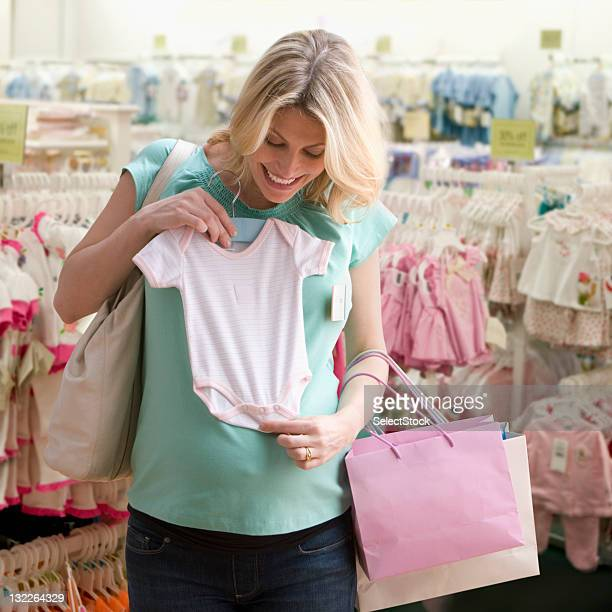 Pregnant woman shopping for baby clothes