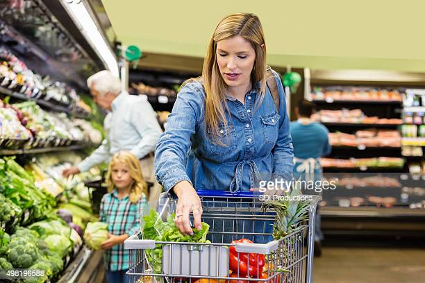 Pregnant woman shopping for healthy groceries in supermarket with daughter