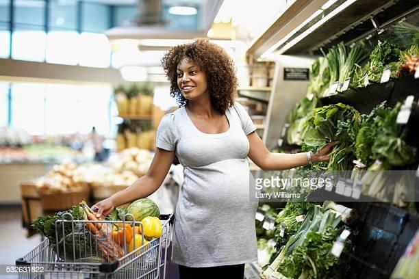 pregnant woman shopping in vegetable aisle - femme noire enceinte photos et images de collection